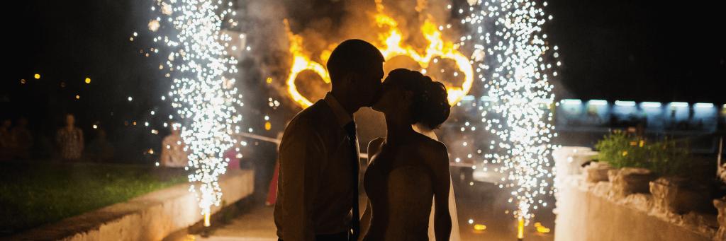 küssendes Brautpaar vor Herzen-Lichterbild mit Sprühfontänen